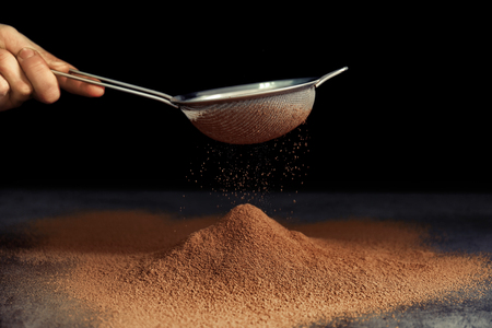 Sieve and powdered cocoa on black background