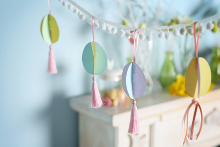 Garland with colorful paper Easter eggs on festive background
