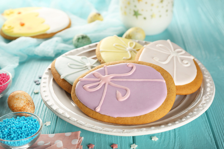 Plate with creative egg shape Easter cookies on wooden background