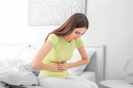 Young sick woman sitting on bed at home