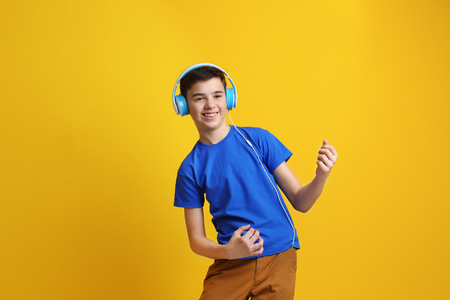 Teenager with headphones listening to music on color background