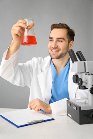 Handsome young scientist testing samples, on light background Stock Photo