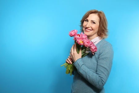 Happy senior woman with bouquet of flowers on color background Imagens
