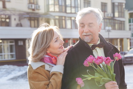 Happy senior couple with bouquet of flowers  on a walk Standard-Bild