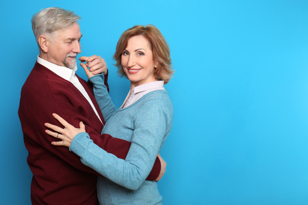 Happy senior couple dancing on color background
