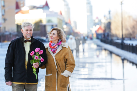 Happy senior couple with bouquet of flowers  on a walk 免版税图像