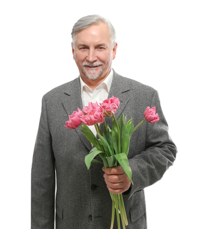 Happy senior man with bouquet of flowers on white background