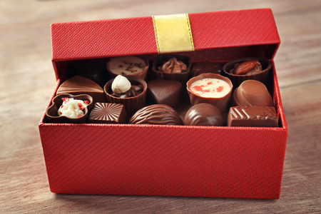 Gift box with delicious candies on wooden background