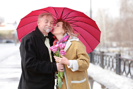 Happy senior couple with bouquet of flowers  standing under umbrella