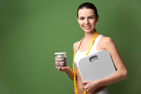 Beautiful young woman with jar of coconut oil and scales on color background