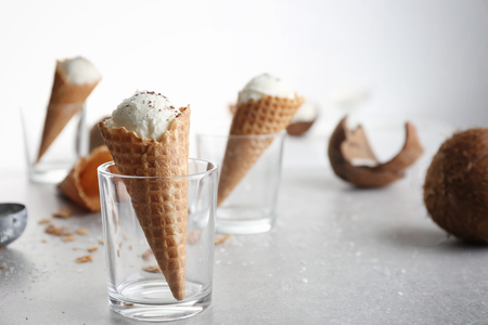 Waffle cone with ball of coconut ice cream in glass on table