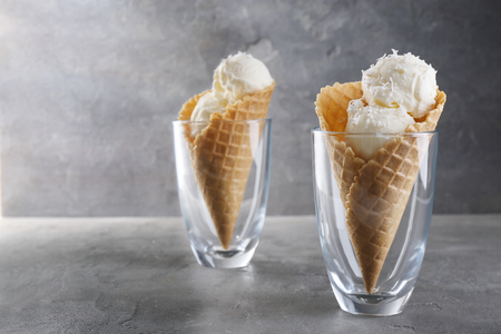 Glasses with waffle cones and balls of coconut ice cream on grunge background Stock Photo