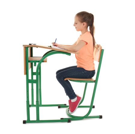 Incorrect posture concept. Schoolgirl sitting at desk on white background