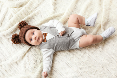 Cute little baby in stylish outfit and funny hat lying on soft blanket