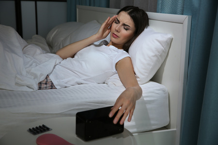 Beautiful young woman suffering from headache while lying in bed at night Фото со стока