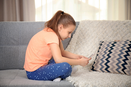Incorrect posture concept. Cute schoolgirl with phone sitting on sofa 스톡 콘텐츠 - 110384545