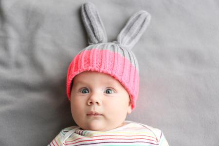 Cute little baby in bunny hat lying on soft blanket
