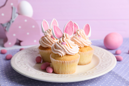 Plate with delicious Easter cupcakes on table