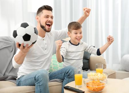 Padre e hijo viendo fútbol en la televisión en casa Foto de archivo