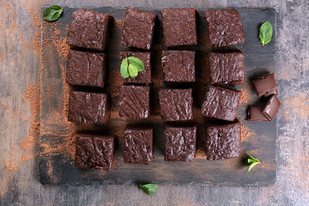 Slate plate with pieces of delicious chocolate brownie Фото со стока
