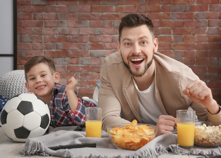 Father and son watching football on TV at home Stock Photo