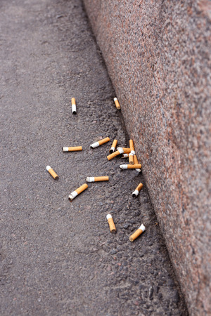 Cigarette butts on asphalt Stock Photo