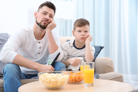 Father and son watching football on TV at home Imagens