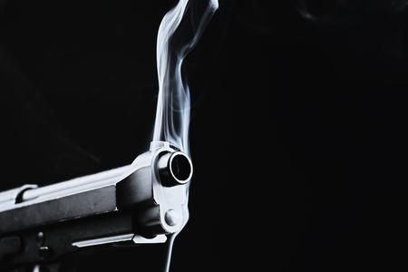 Pistola humeante sobre fondo negro