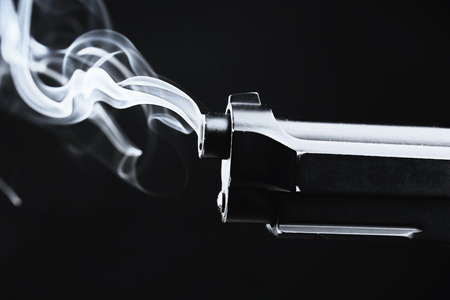 Smoking gun on black background 免版税图像