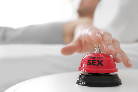 Man ringing sex bell on table near bed Stock Photo