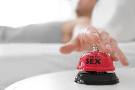 Man ringing sex bell on table near bed Kho ảnh