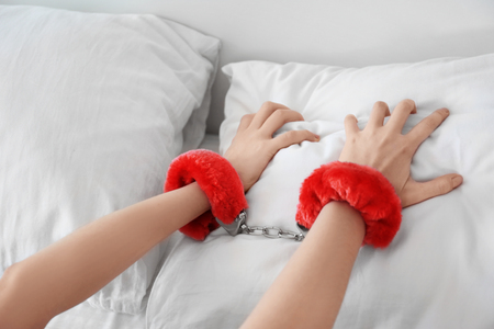 Woman wearing sexy fluffy handcuffs on her wrists in bed