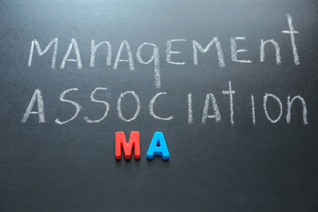 Abbreviation and text written with chalk on table. Management concept