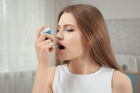 Young woman using asthma inhaler at home