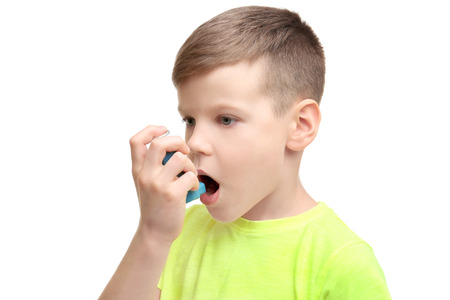 Little boy using asthma inhaler on white background Foto de archivo