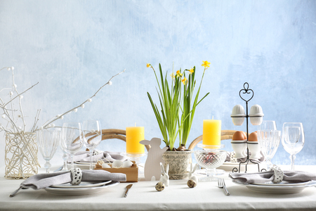 Beautiful Easter table setting in light room Imagens