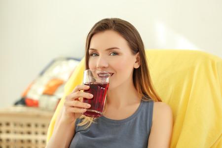 Beautiful woman drinking fresh juice at home