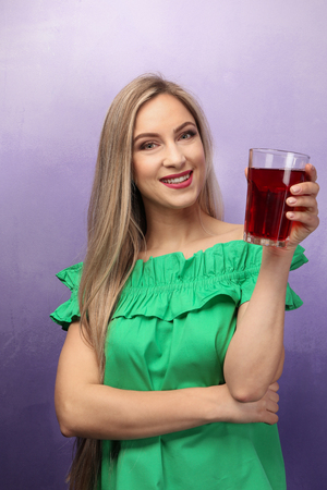 Beautiful young woman with glass of fresh juice on color background Stock Photo
