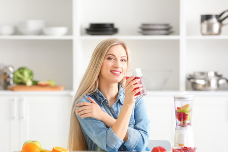 Beautiful young woman with glass of fresh juice in kitchen 免版税图像