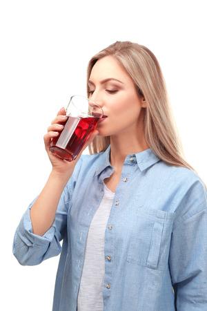 Beautiful young woman drinking fresh juice on white background Stock Photo