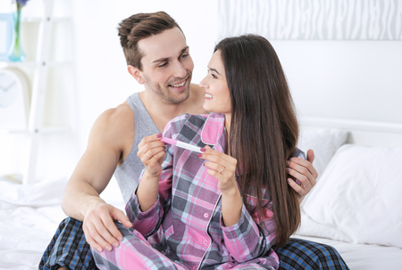 Married couple sitting on bed with pregnancy test Stockfoto