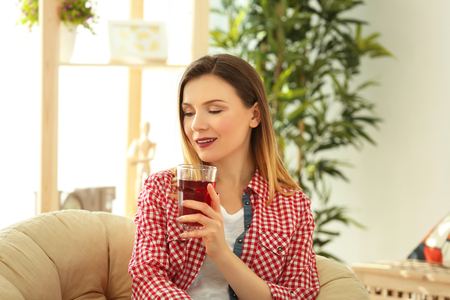 Beautiful woman with glass of fresh juice at home Stock Photo