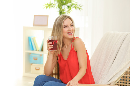 Beautiful young woman with glass of fresh juice at home