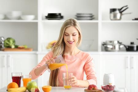 Beautiful young woman preparing fresh juice in kitchen