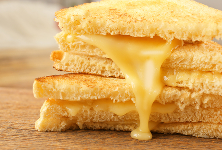 Grilled bread and melting cheese on wooden surface, closeup