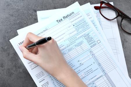 Mujer rellenando el formulario de impuesto sobre la renta de las personas físicas, primer plano