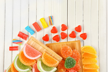 Composition of tasty jelly candies on wooden background Banco de Imagens