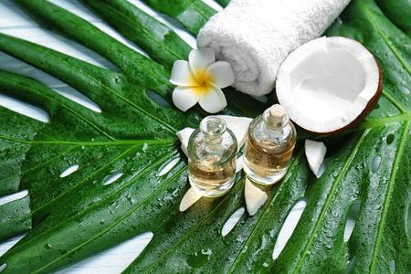 Bottles of oil, coconut, towel, tropical flower on green leaf