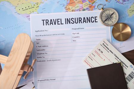Modulo vuoto di assicurazione di viaggio e mappa sullo sfondo