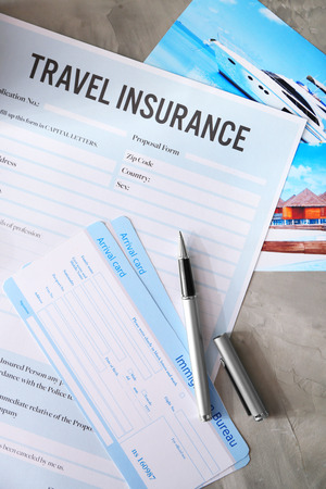Arrival cards and pen on blank travel insurance form, closeup Banco de Imagens